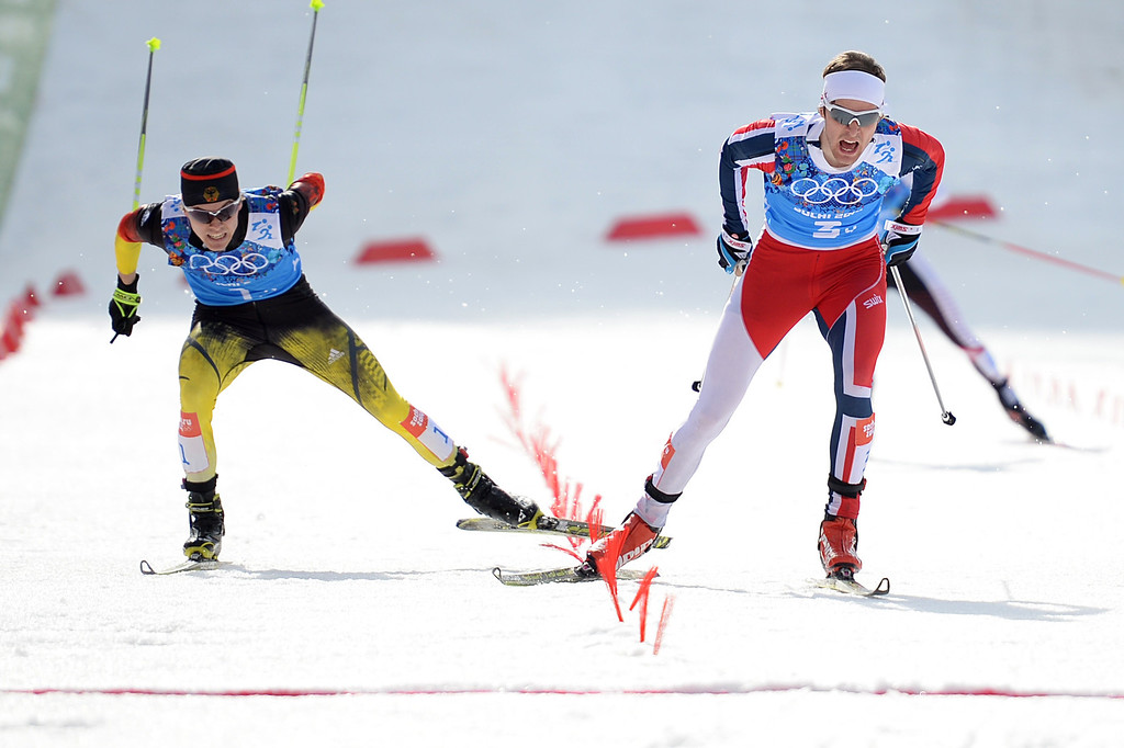 . Norway\'s Joergen Graabak crosses the finish line to snatch gold as silver medalist Germany\'s Fabian Riessle follows behind in the Nordic Combined Team LH / 4x5 km Cross-Country at the RusSki Gorki Jumping Center during the Sochi Winter Olympics on February 20, 2014, in Rosa Khutor near Sochi. PETER PARKS/AFP/Getty Images