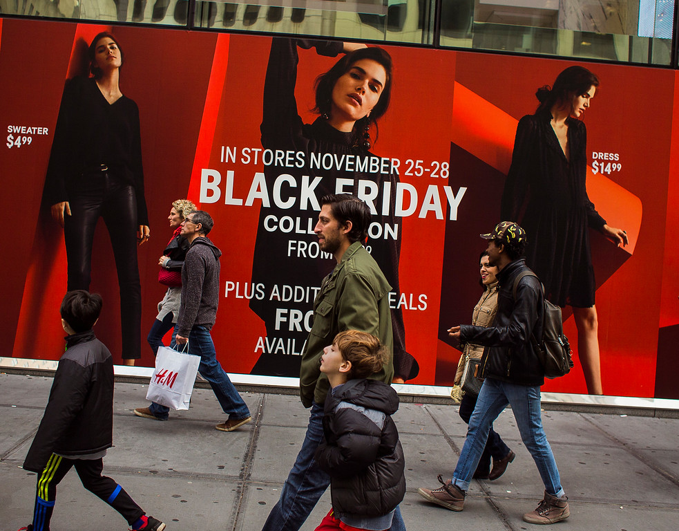 . Shoppers pass by a retail store as they walk along Fifth Avenue on Black Friday in New York, Friday, Nov. 25, 2016. Shoppers were on the hunt for deals Friday as malls opened for what is still one of the busiest days of the year, even as the start of the holiday season edges ever earlier. (AP Photo/Andres Kudacki)