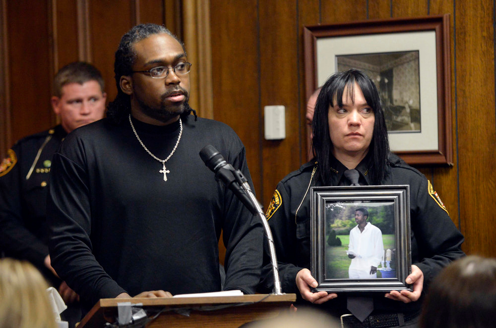 Description of . Philip Carter, brother of Demetrius Hewlin, reads a statement on behalf of his mother, during the sentencing of T.J. Lane on Tuesday, March 19, 2013, in Chardon, Ohio.  Lane was given three lifetime prison sentences without the possibility of parole Tuesday for opening fire last year in a high school cafeteria in a rampage that left three students dead and three others wounded.  Hewlin was one of three students killed. Lane, 18, had pleaded guilty last month to shooting at students in February 2012 at Chardon High School, east of Cleveland.   (AP Photo/The News-Herald, Duncan Scott, Pool)