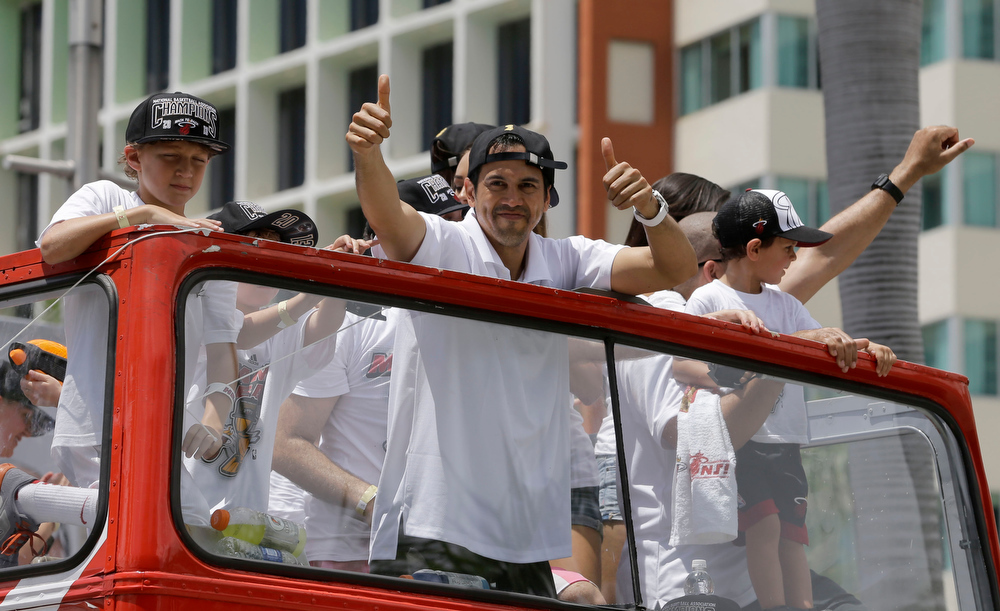 . NBA champion Miami Heat head coach Erik Spoelstra, center,  gestures to fans during a parade honoring the team in Miami, Monday, June 24, 2013.  (AP Photo/Alan Diaz)