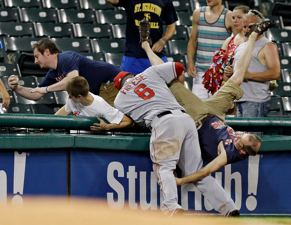 . A fan falls out of the stands as Los Angeles Angels third baseman David Freese (6) tries for a pop foul by Cleveland Indians\' Carlos Santana in the ninth inning of a baseball game Tuesday, June 17, 2014, in Cleveland. The Angels won 9-3. (AP Photo/Mark Duncan, File)