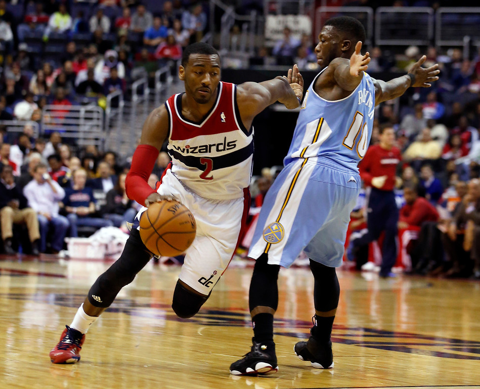 . Washington Wizards guard John Wall (2) gets past Denver Nuggets guard Nate Robinson (10) in the second half of an NBA basketball game on Monday, Dec. 9, 2013, in Washington. The Nuggets won 75-74. (AP Photo/Alex Brandon)