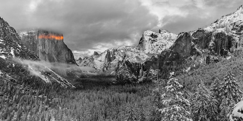 """On the top of my photography bucket list has been to witness and photograph a snowy Yosemite. This year I've paid close attention to the snow in Yosemite and finally during my Christmas break I had my chance to see Yosemite covered in snow! A giant storm had just hit the Eastern Sierras and dumped about 10 feet of snow (in fact, Kirkwood received 7 feet in ONE DAY!). Willie, Alan, Sammi and I planned on arriving just as the storm cleared. Unfortunately by the time we rented a 4-wheel drive vehicle and made our way through chain control and into Yosemite most of the storm had gone. The radar showed more clouds coming and we held our breath that sunset would be nice.  After visiting several stops around the Yosemite Valley and running into a couple other photographers that we knew we settled on returning to Tunnel View for sunset. Joined by a gazillion other photographers (or a """"meat market"""" as Breezy would call it) we witnessed a beautiful sunset. Although the clouds did not light up with much color there was an absolutely beautiful stripe of color that appeared on El Capitan, as some clouds made enough room for the light to seep in.   I combined 7 vertical images in Photoshop to create this 2x1 panorama of a snowy Yosemite. With snow on the trees and a pale, boring, blue color in the sky I knew that this photograph had to be done in black and white. I couldn't help but love the red color that was caste across El Capitan and decided to selectively bring this back in. Fog crept in as the sun began to set and creates a nice mystical mood to the photo.  I printed this as a 24""""x48"""" lustre print on Gatorboard and hung it in my office at my apartment! It looks great on the wall!  Nikon D800 w/Nikkor 24-70mm f/2.8G ED AF-S: 70mm, f/11, 1/4 sec, ISO 100 7 images stitched in Photoshop"""