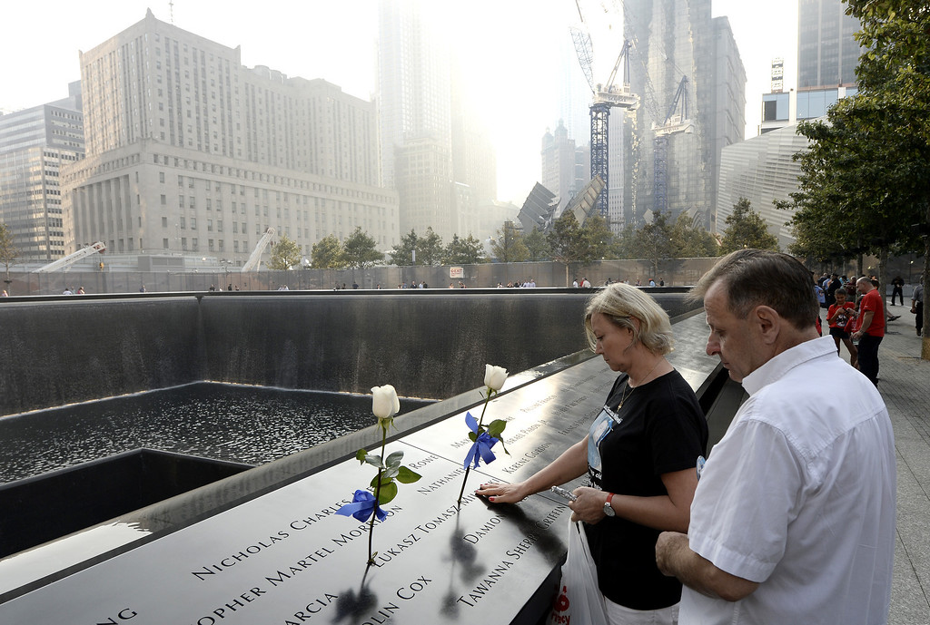 . A couple pauses along the edge of the North Pool at the 9/11 Memorial during ceremonies for the twelfth anniversary of the terrorist attacks on lower Manhattan at the World Trade Center site on September 11, 2013 in New York City.  (Photo by Justin Lane-Pool/Getty Images)