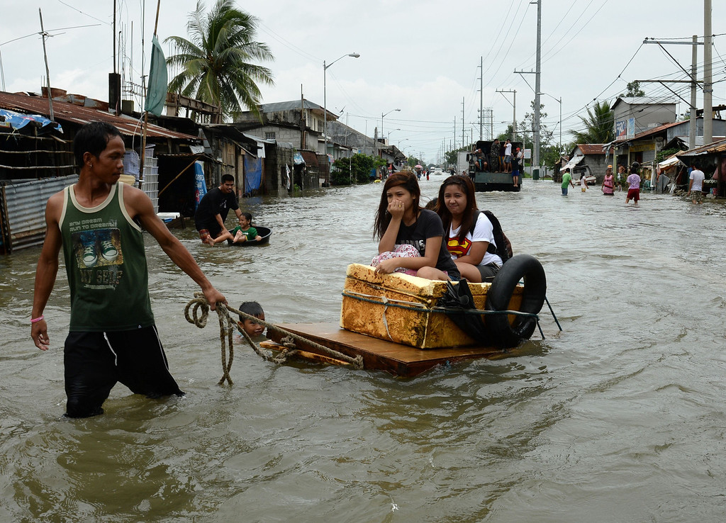 . Residents affected by flooding due to heavy rains exarcebated by Tropical storm Trami are transported on a makeshift raft along a flooded street in the town of Calumpit, Bulacan province, north of Manila on August 22, 2013. Disaster-weary Philippine residents mopped up August 22 after four days of rains that officials said had killed 18 people and forced more than half a million from flooded homes. TED ALJIBE/AFP/Getty Images