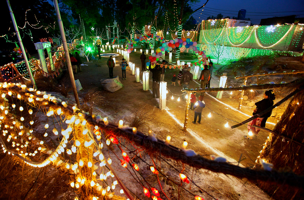 . Pakistani Christians walk in an enclosure specially decorated for Christmas celebrations, at a Christian neighborhood of Islamabad, Pakistan, Sunday, Dec. 24, 2017. (AP Photo/Anjum Naveed)