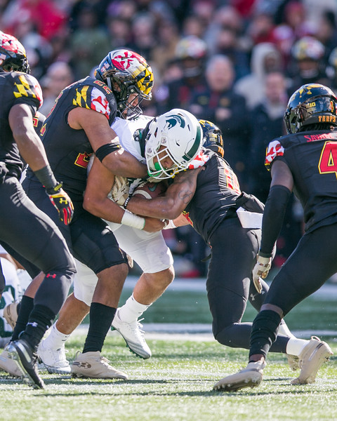 Michigan State RB #11 Connor Heyward fights for extra yards against Maryland defenders