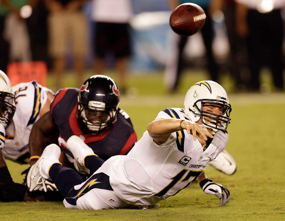 . San Diego Chargers quarterback Philip Rivers, right, throws under pressure from Houston Texans outside linebacker Whitney Mercilus during the first half of an NFL football game Monday, Sept. 9, 2013, in San Diego. (AP Photo/Gregory Bull)
