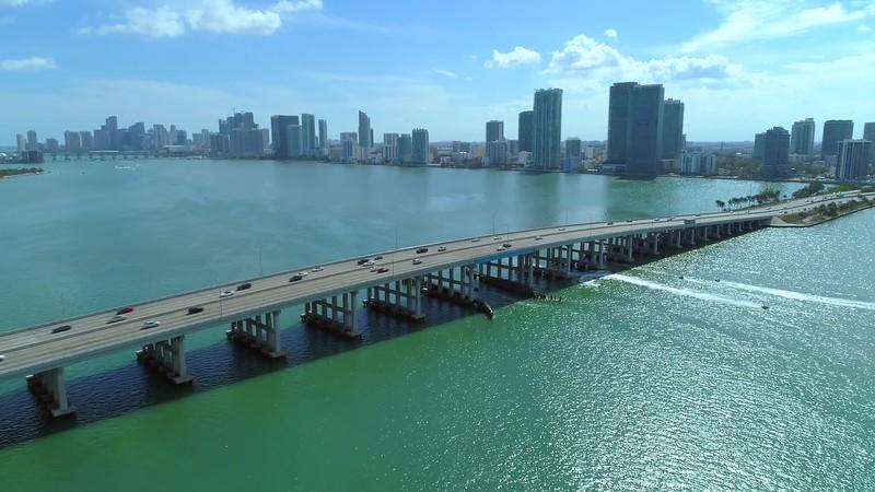 Aerial drone Miami flyover bridge tilt down cinematic turn