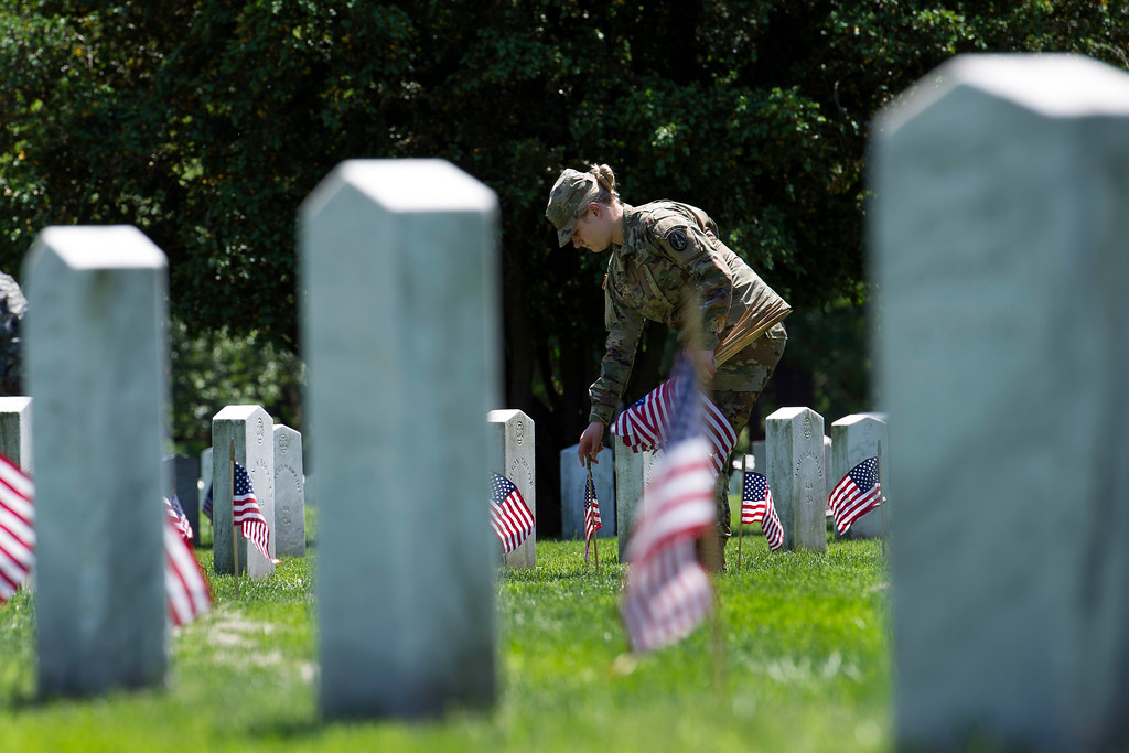 . A soldier with the Army 3d U.S. Infantry Regiment, The Old Guard, places a flag at the headstone, as the Regiment honors the nation\'s fallen military heroes during its annual Flags In ceremony at Arlington National Cemetery, May 24, 2018, in Arlington, Va. (AP Photo/Cliff Owen)