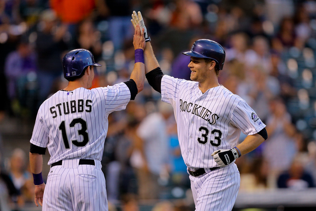 . DENVER, CO - SEPTEMBER 6:  Justin Morneau #33 of the Colorado Rockies is congratulated by Drew Stubbs #13 after hitting a two run home run during the third inning against the San Diego Padres at Coors Field on September 6, 2014 in Denver, Colorado. (Photo by Justin Edmonds/Getty Images)