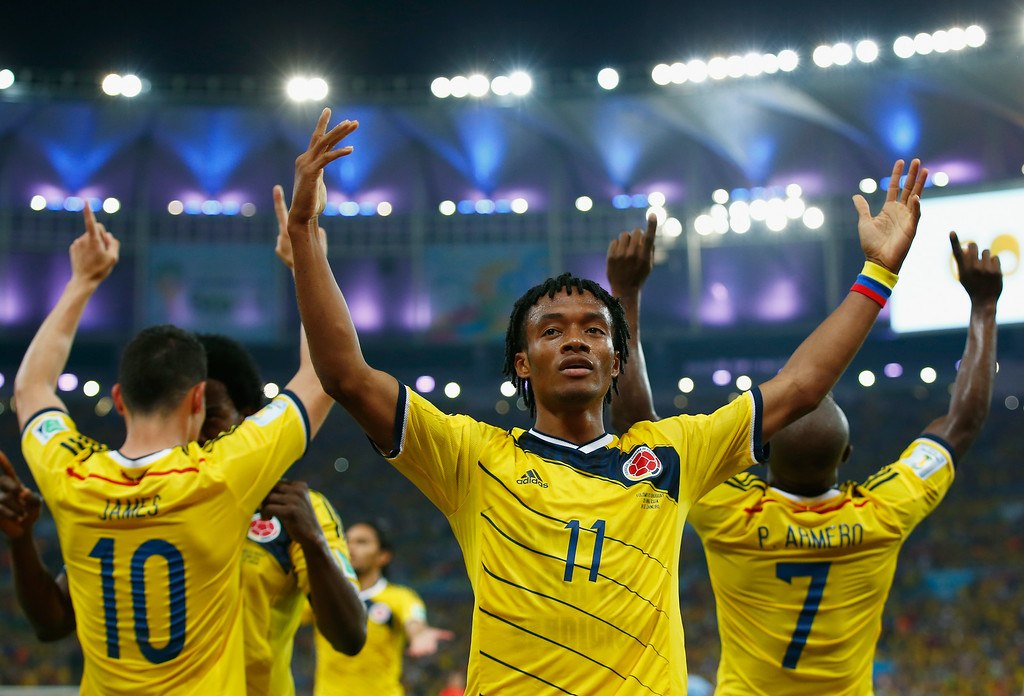 . RIO DE JANEIRO, BRAZIL - JUNE 28: Juan Guillermo Cuadrado of Colombia celebrates his team\'s second goal scored by James Rodriguez (L) during the 2014 FIFA World Cup Brazil round of 16 match between Colombia and Uruguay at Maracana on June 28, 2014 in Rio de Janeiro, Brazil.  (Photo by Clive Rose/Getty Images)