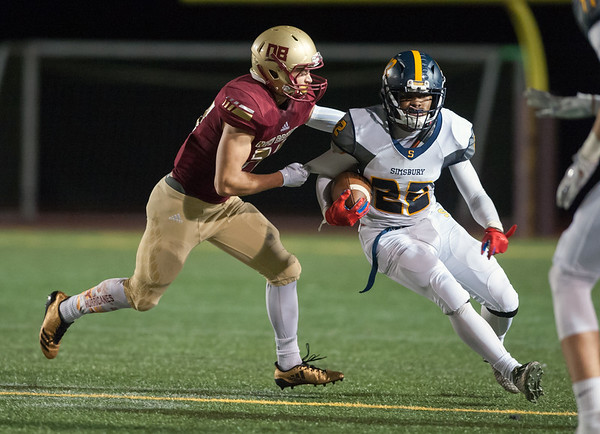 09/28/18 Wesley Bunnell | Staff New Britain football vs Simsbury on Friday night at Veterans Stadium. Hubert Lanoszka (27) prepares to wrap up the Simsbury receiver.