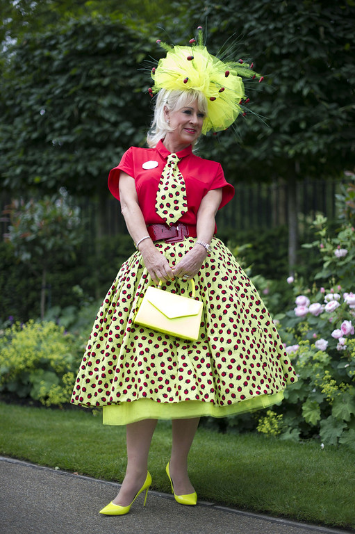 . A race-goer poses for photographers on Ladies Day at the annual Royal Ascot horse racing event near Windsor, Berkshire on June 19, 2014. AFP PHOTO / CARL COURT/AFP/Getty Images