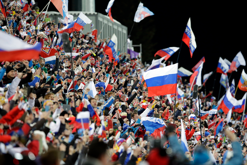 . Fans wave flags as they celebrate after Russia won the men\'s biathlon 4x7.5K relay at the 2014 Winter Olympics, Saturday, Feb. 22, 2014, in Krasnaya Polyana, Russia. (AP Photo/Lee Jin-man)