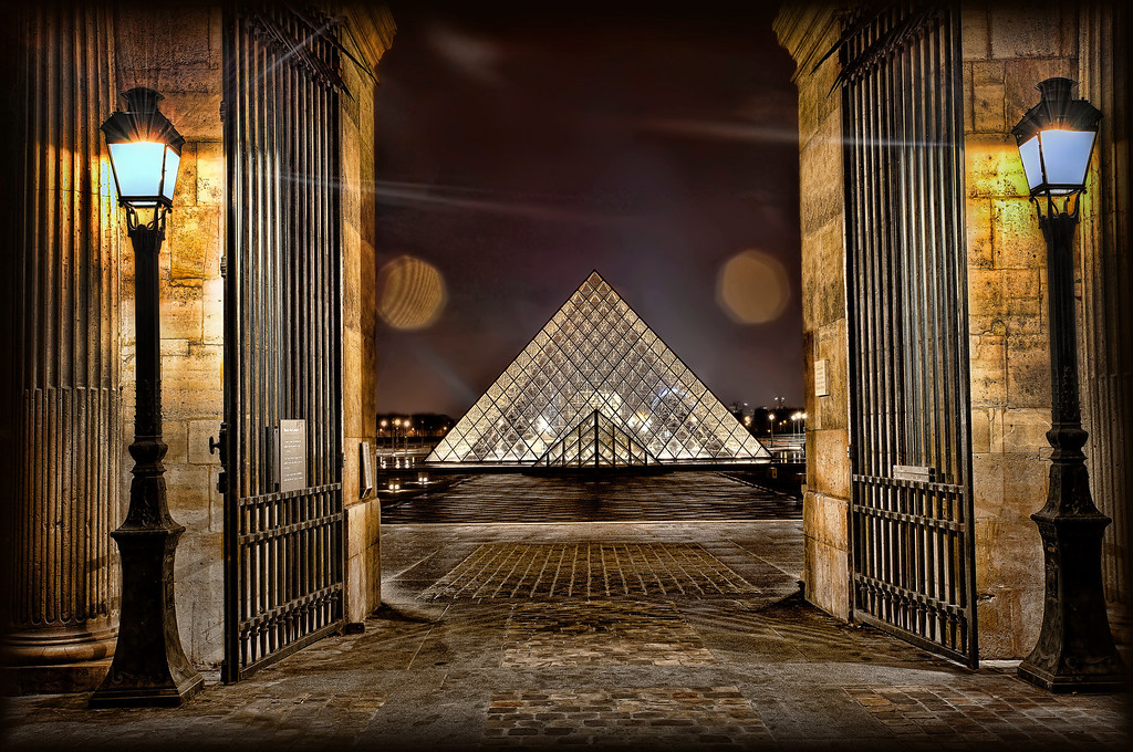 <h2> Then and Now </h2> The Louvre, Paris. Closing time. The security guard was very kind and waited patiently - then closed the gates behind us.   The Louvre was originally a moated castle with towers commissioned by King Philip Augustus, aka Philip II.  He was alive and kicking from 1165-1223. So you get the idea on age. This is what you see if you stand in the oldest part of today's Louvre - the Cour Caree - and look into the main courtyard where the newest part sits. It's like the entire history of the place suddenly folds into one moment of simultaneity.  A single wrinkle in time.  Ya gotta love a good juxtaposition.