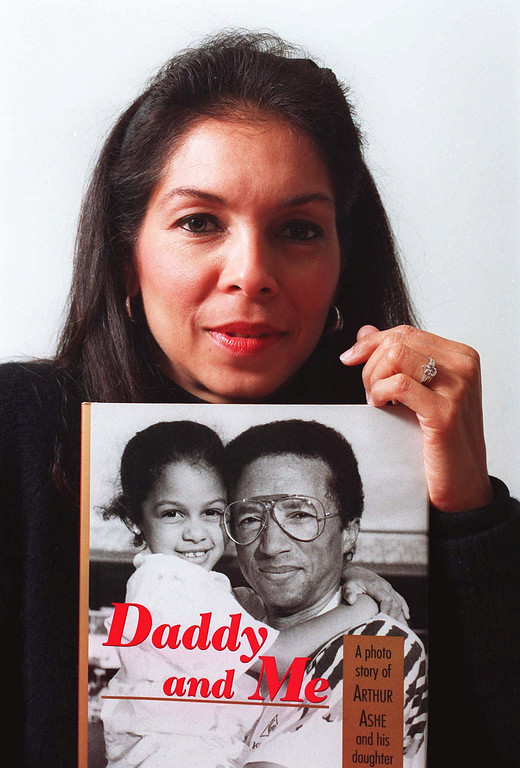 ". Jeanne Ashe poses with a copy of her book ""Daddy and Me\""at the Studio Museum in Harlem Dec.1, 1993 in New York. Ashe photographed the family album that tells of her late husband\'s last year with their daughter, Camera. Arthur Ashe died of AIDS on Feb. 6,1993. Jeanne Ashe signed copies of her book at the museum  as part of AIDS Awareness Day.(AP Phaoto/Mark Lennihan)"