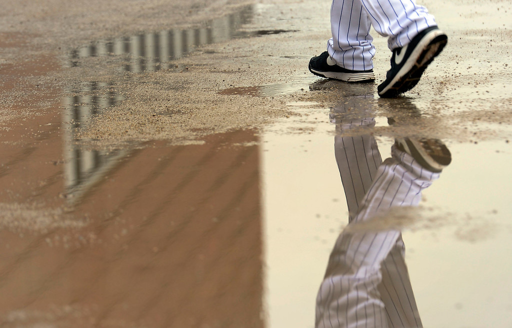 . SCOTTSDALE, AZ. - FEBRUARY 20: Colorado Rockies players walk through the puddles during a short day hitting in the batting cages due to rain during Spring Training  February 20, 2013 in Scottsdale. (Photo By John Leyba/The Denver Post)