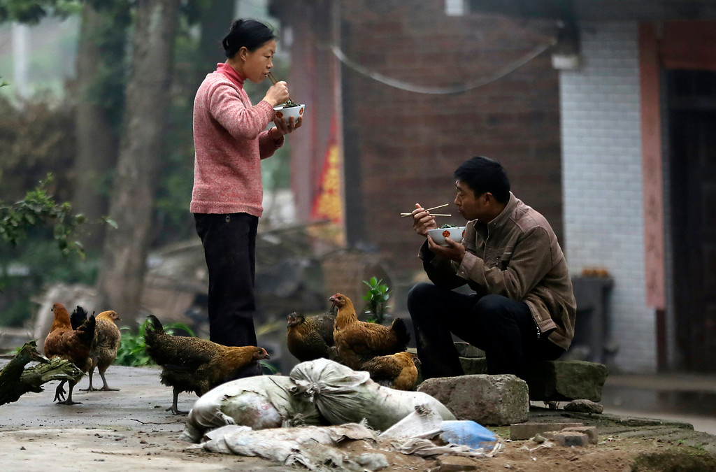 . Farmers eat their meals on the outskirts of Chongqing, China on Tuesday March 19, 2013. (AP Photo/Eugene Hoshiko)