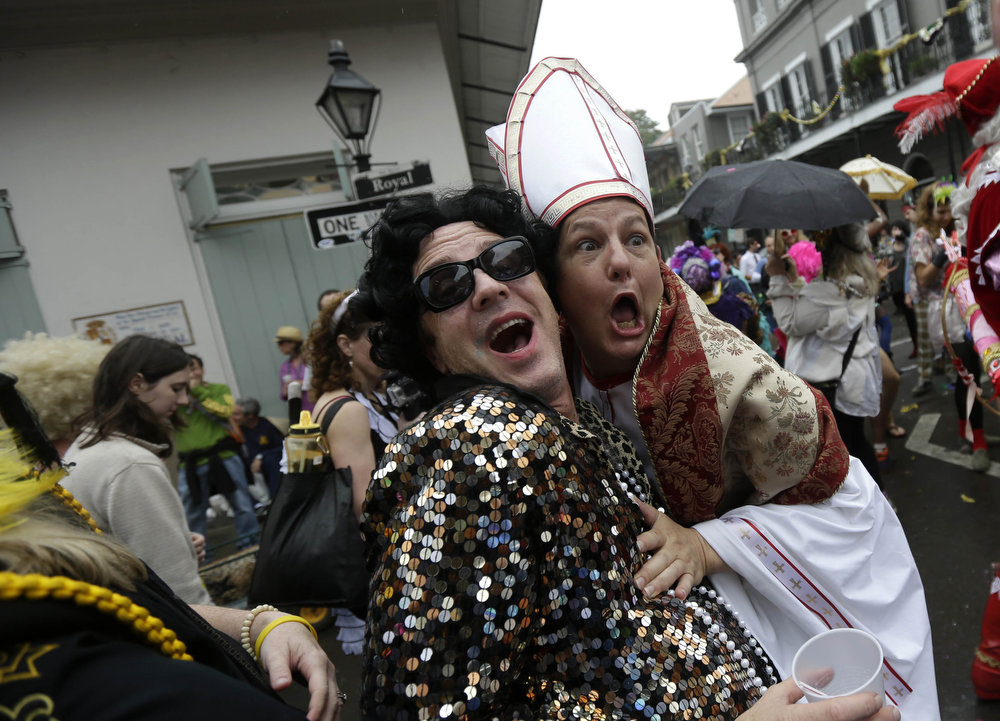 . A man dressed as the Pope revels with other costumed people during Mardi Gras in the French Quarter of New Orleans, Tuesday, Feb. 12, 2013. Despite threatening skies, the Mardi Gras party carried on as thousands of costumed revelers cheered glitzy floats with make-believe monarchs in an all-out bash before Lent.   Crowds were a little smaller than recent years, perhaps influenced by the forecast of rain. Still, parades went off as scheduled even as a fog settled over the riverfront and downtown areas. (AP Photo/Gerald Herbert)