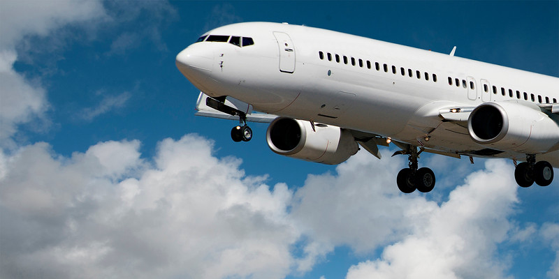 Aircraft closeup in flight with cumulus cloud in blue sky. Australia.