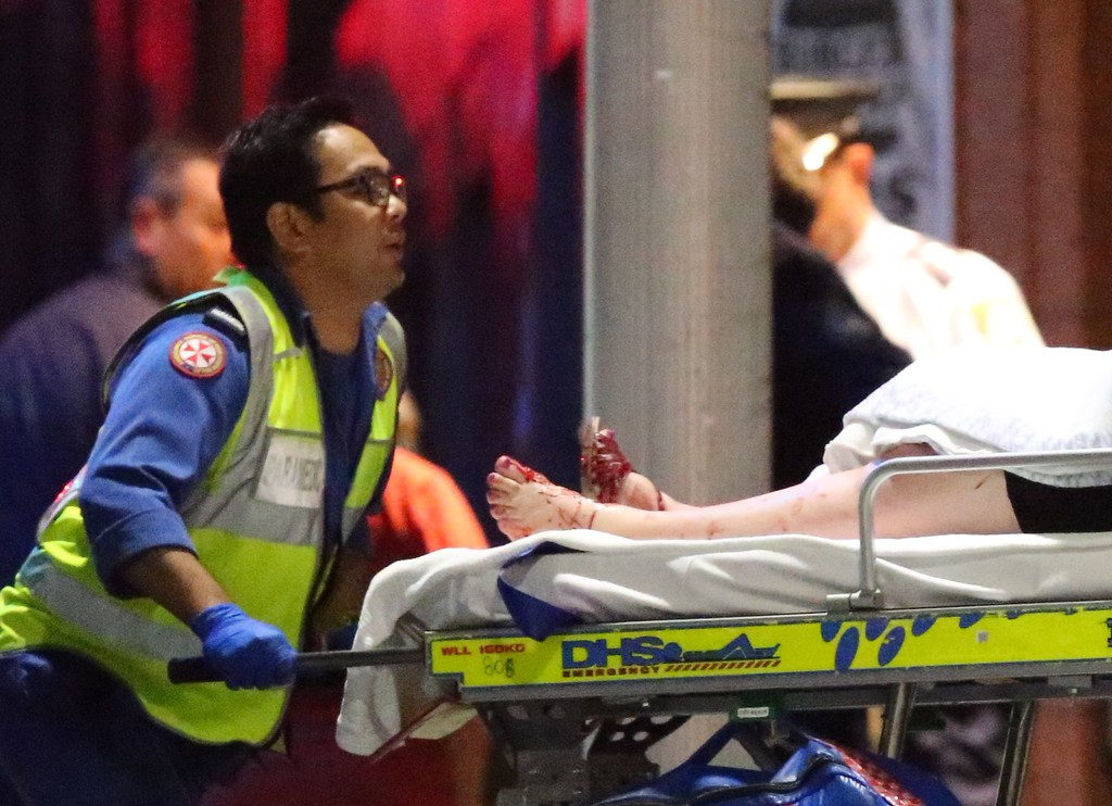 . A injured hostage is wheeled to an ambulance after shots were fired during  a cafe siege at Martin Place in the central business district of Sydney, Australia, Tuesday, Dec. 16, 2014. A flurry of loud bangs erupted as a swarm of heavily armed police stormed inside a downtown Sydney chocolate cafe where a gunman had been holding an unknown number of people hostage for more than 16 hours. (AP Photo/Rob Griffith)