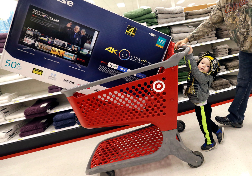 . Hunter Harvey, 2, helps his dad, C.J., wheel a big screen TV at Target on Black Friday, Nov. 25, 2016, in Wilmington, Mass. Stores open their doors Friday for what is still one of the busiest days of the year, even as the start of the holiday season edges ever earlier. (AP Photo/Elise Amendola)