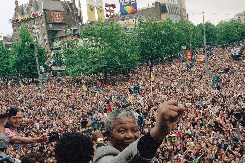 Description of . South African leader of the ANC Nelson Mandela raises his fist after addressing a crowd of about 15,000 people from the balcony of the city theater Saturday, June 16, 1990  in Amsterdam. Mandela is on a one-day visit in the Netherlands. On the left seen from the back his wife Winnie. (AP Photo/Rob Croese)