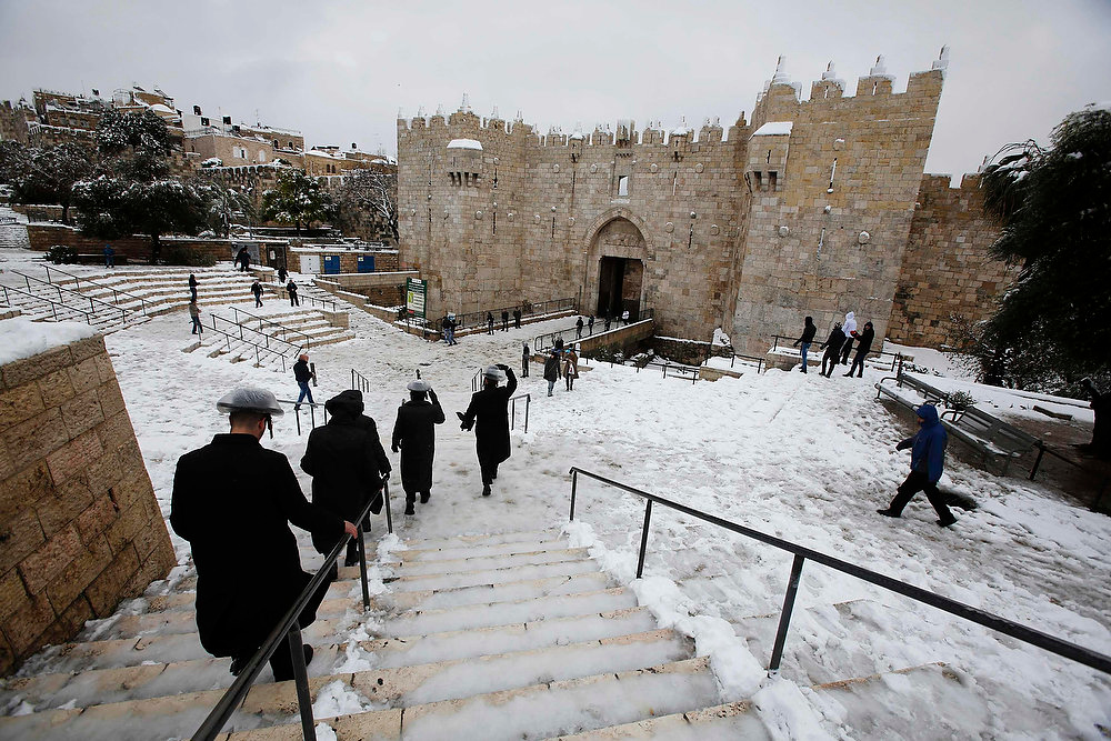 Description of . Ultra-Orthodox Jewish men walk down snow-covered steps in front of Damascus Gate in Jerusalem's Old City on January 10, 2013. The worst snowstorm in 20 years shut government offices, public transport and schools in Jerusalem and along the northern Israeli region bordering on Lebanon on Thursday.  REUTERS/Baz Ratner