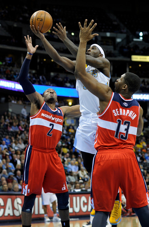 . DENVER, CO - JANUARY 18: Denver guard Ty Lawson cut between Washington defender John Wall and Kevin Seraphin in the first half. The Denver Nuggets hosted the Washington Wizard at the Pepsi Center Friday night, January 18, 2013. Karl Gehring/The Denver Post