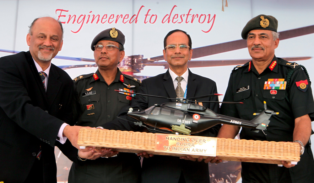 Description of . Lieutenant General of the Indian Army, Narendra Singh, (R), HAL Chairman, R.K. Tyagi,(2R), Major General, AOG (Army Aviation) General P.K. Bharali, (2L) and Managing Director of HAL, P. Sounderajan pose for a photograph during the handing over of the Light Combat Helicopter (LCH), 'Rudra' to the Indian Army on the third day of the 9th edition of the Aero India 2013 at Yelahanka Air Force station in Bangalore on February 8, 2013.    India, the world's leading importer of weaponry, opened one of Asia's biggest aviation trade shows February 6 with Western suppliers eyeing lucrative deals and a Chinese delegation attending for the first time.  AFP/Manjunath KIRANManjunath Kiran/AFP/Getty Images