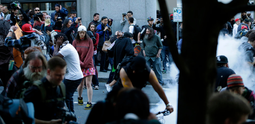 . Protesters react as a police flash-bang grenade goes off during a May Day march that began as an anti-capitalism protest and turned into demonstrators clashing with police Wednesday, May 1, 2013, in downtown Seattle. (AP Photo/Ted S. Warren)