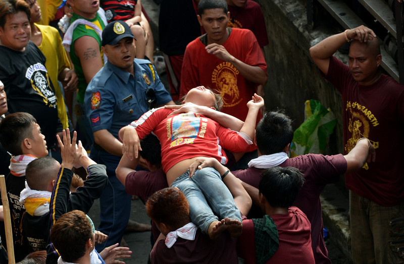 . An unconscious devotee is carried to the nearest red cross in central Manila on January 9, 2013.  Masses of Catholic devotees swept through the Philippine capital on Wednesday in a spectacular outpouring of passion for a centuries-old statue of Jesus Christ that many believe can perform miracles. In the nation\'s biggest annual religious festival, barefoot men and women crammed into Manila\'s streets hoping to touch the life-sized, black icon as it was paraded through the city\'s historic area for a day-long procession.  JAY DIRECTO/AFP/Getty Images