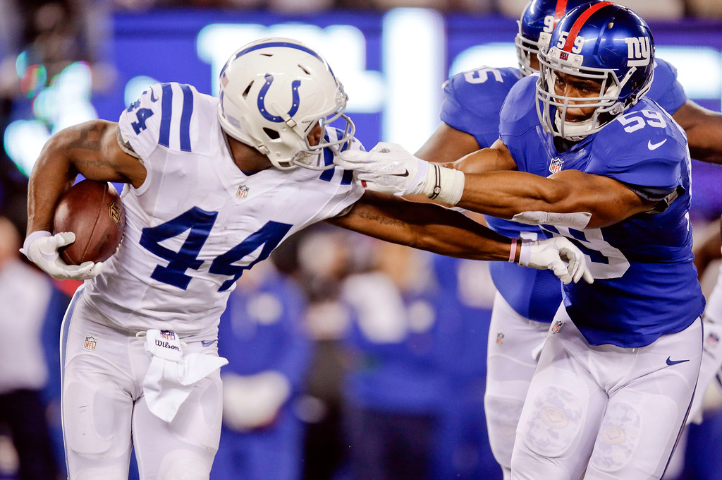 . New York Giants outside linebacker Devon Kennard (59) grabs the face mask of Indianapolis Colts\' Ahmad Bradshaw (44) during the first half of an NFL football game Monday, Nov. 3, 2014, in East Rutherford, N.J. (AP Photo/Kathy Willens)