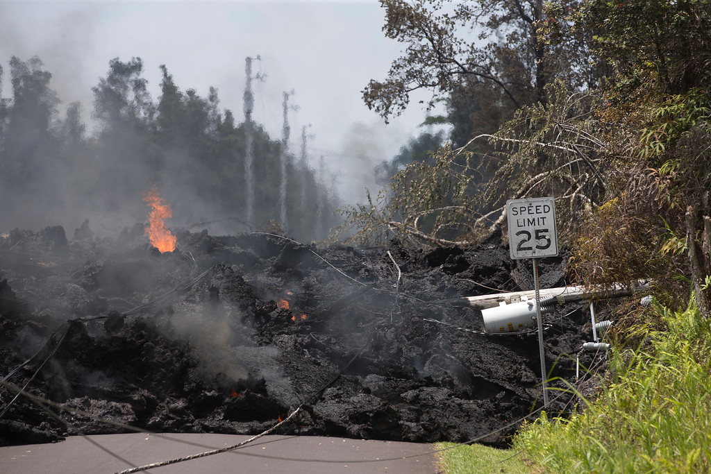 . Power lines are pulled down by lava in the Leilani Estates, Saturday, May 5, 2018, in Pahoa, Hawaii. The Hawaiian Volcanoes Observatory said eight volcanic vents opened in the Big Island residential neighborhood of Leilani Estates since Thursday. (AP Photo/Marco Garcia)