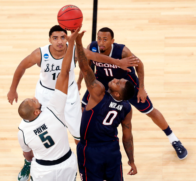 . Michigan State forward Adreian Payne (5) and Connecticut forward Phillip Nolan (0) go up for the tip-off as Michigan State\'s Gary Harris, top left, and Connecticut\'s Keith Appling (11) look on during the first half in a regional semifinal at the NCAA college basketball tournament on Sunday, March 30, 2014, in New York. (AP Photo/Julio Cortez)