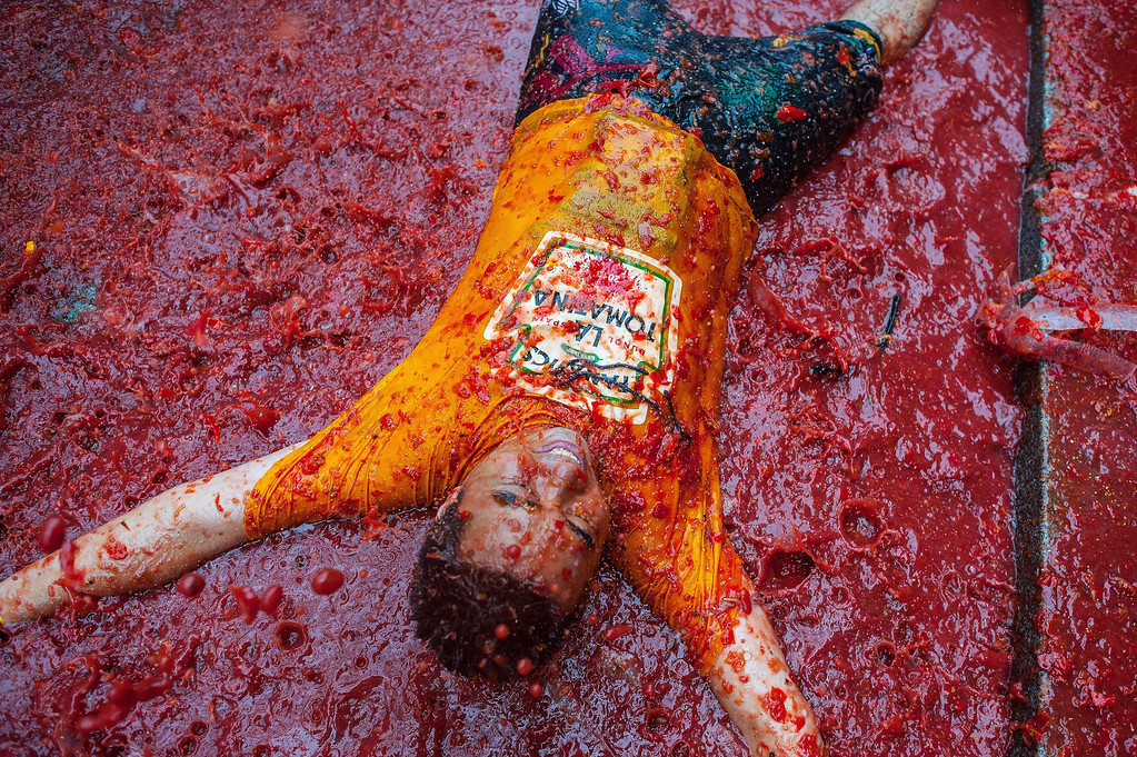 . A reveler bathes in tomato pulp while participating the annual Tomatina festival on August 28, 2013 in Bunol, Spain. An estimated 20,000 people threw 130 tons of ripe tomatoes in the world\'s biggest tomato fight held annually in this Spanish Mediterranean town.  (Photo by David Ramos/Getty Images)