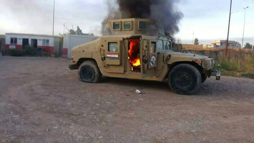 . A picture taken with a mobile phone shows an armoured vehicle belonging to Iraqi security forces in flames on June 10, 2014,  after hundreds of militants from the Islamic State of Iraq and the Levant (ISIL) launched a major assault on the security forces in Mosul, some 370 kms north from the Iraqi capital Baghdad. Some 500,000 Iraqis have fled their homes in Iraq\'s second city Mosul after Jihadist militants took control, fearing increased violence, the International Organization for Migration said. STR/AFP/Getty Images