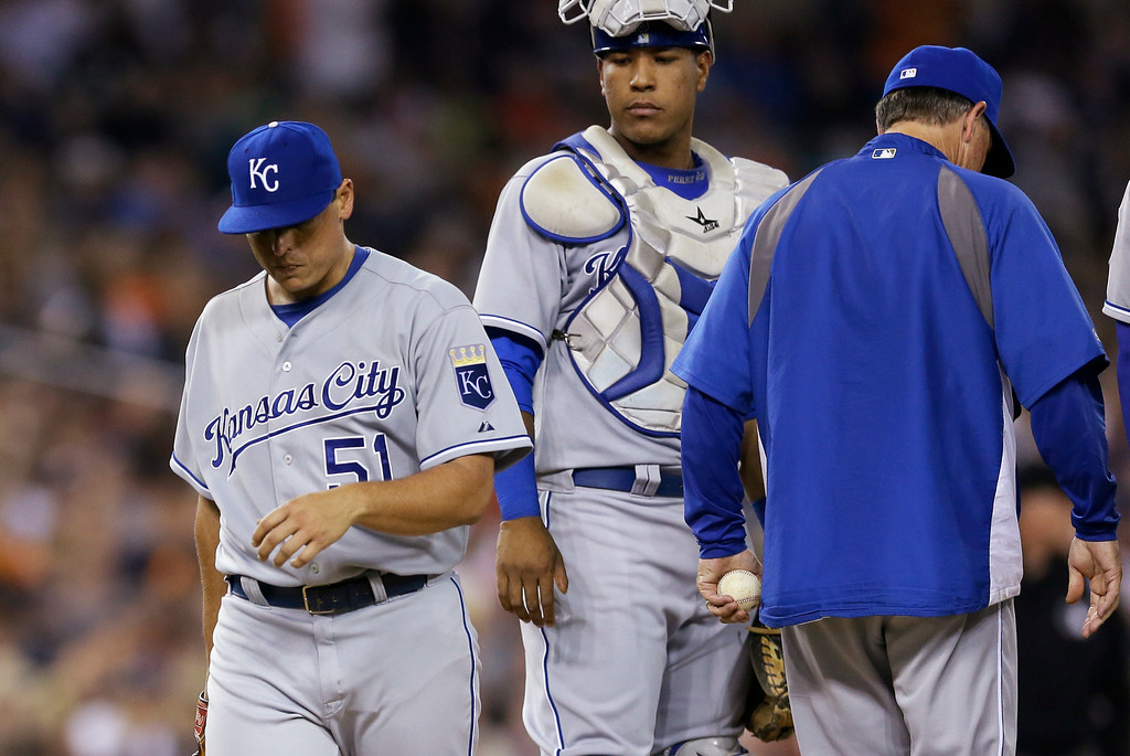 . Kansas City Royals starting pitcher Jason Vargas, left, walks off the mound after being relieved by manager manager Ned Yost during the sixth inning of a baseball game against the Detroit Tigers in Detroit, Tuesday, Sept. 9, 2014. (AP Photo/Carlos Osorio)