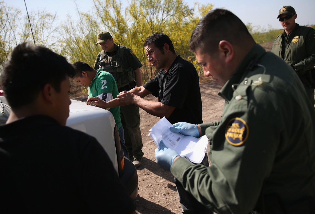 . MISSION, TX - APRIL 11:  U.S. Border Patrol agents detain undocumented immigrants near the U.S.-Mexico border on April 11, 2013 near Mission, Texas. A group of 16 immigrants from Mexico and El Salvador said they crossed the Rio Grande River from Mexico into Texas during the morning hours before they were caught. The Rio Grande Valley sector of has seen more than a 50 percent increase in illegal immigrant crossings from last year, according to the Border Patrol. Agents say they have also seen an additional surge in immigrant traffic since immigration reform negotiations began this year in Washington D.C. Proposed refoms could provide a path to citizenship for many of the estimated 11 million undocumented workers living in the United States. Photo by John Moore/Getty Images)  (Photo by John Moore/Getty Images)