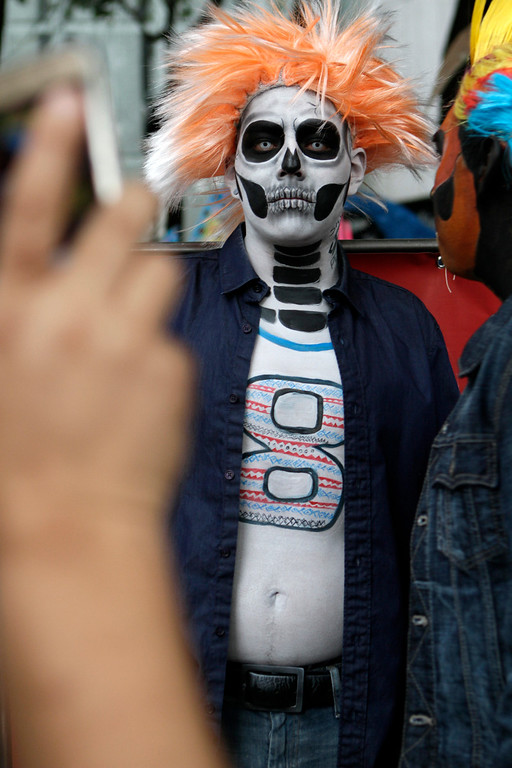 . Carlos Ramirez, dressed as a calavera, poses for a photo as he waits for the start of the Gran Procession of the Catrinas, to mark the upcoming Day of the Dead holiday, in Mexico City, Sunday, Oct. 23 2016. The gran procession is one of many that will take place in Mexico City as part of the celebrations, culminating with visits to the graves of departed loved ones on Nov. 1 and 2. The figure of a skeleton wearing broad-brimmed hat was first done as a satirical engraving by artist Jose Guadalupe Posada sometime between 1910 and his death in 1913, to poke fun at women who pretended to be European by dressing elegantly and as a critique of social stratification. (AP Photo/Anita Baca)