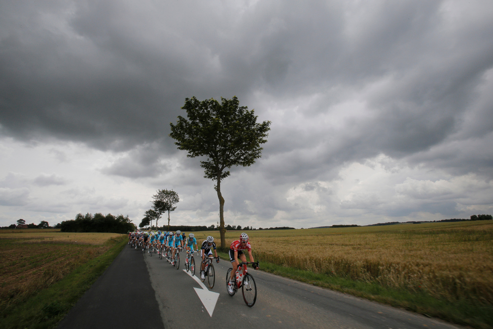 Description of . Rain clouds spell trouble for the riders as the pack heads towards Lille during the fourth stage of the Tour de France cycling race over 163.5 kilometers (101.6 miles) with start in Le Touquet and finish in Lille, France, Tuesday, July 8, 2014. The hectic pace of the first week combined with wet roads are at the origin of crashes in the pack. (AP Photo/Christophe Ena)