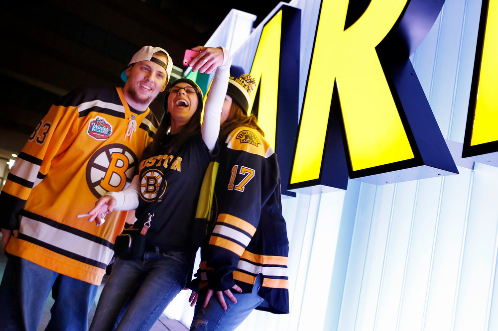 Description of . Boston Bruins fans, from left, Derek Thibault, of Bradford, Mass., Kayleigh Conway, of Londonderry, N.H., and Katy Epstein, also of Bradford, Mass., photograph themselves outside TD Garden before an NHL hockey game between the Bruins and the New York Rangers in Boston, Saturday, Jan. 19, 2013. (AP Photo/Michael Dwyer)