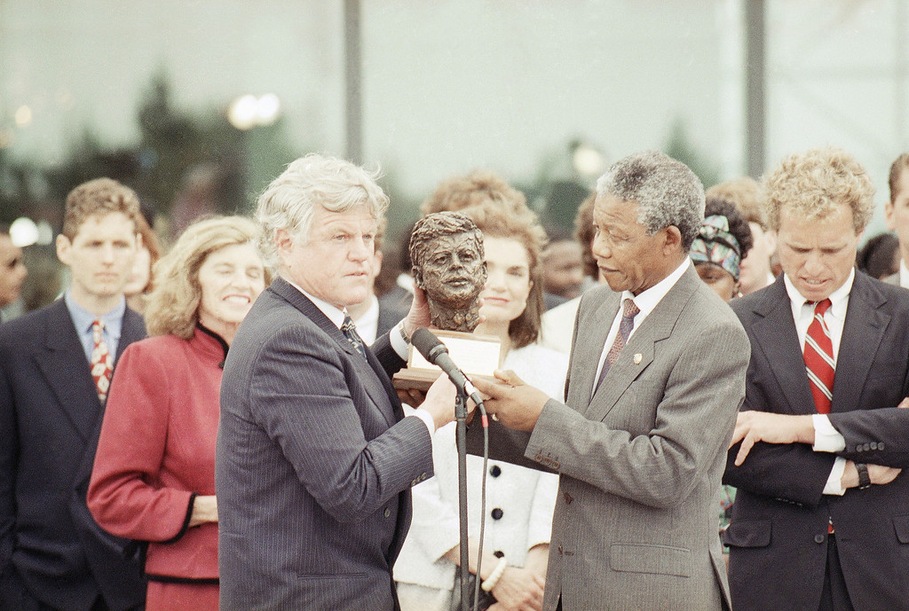 . Nelson Mandela receives a bust of the late president John F. Kennedy from the president\'s brother Sen. Edward Kennedy, left, during a ceremony at the John F. Kennedy library in Boston Saturday, June 23, 1990.  At far right is Jacqueline Kennedy Onassis.  Eunice Shriver, sister of Sen. Kennedy looks on behind Mandela.  At right is Joe Kennedy II, son of Robert Kennedy.   (AP Photo/Charles Krupa)