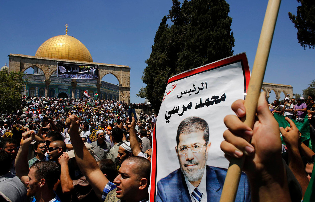 . A Palestinian holds a picture of ousted Egyptian president Mohamed Mursi as some pro-Mursi supporters demonstrate after prayers in front of the Dome of the Rock on the compound known to Muslims as Noble Sanctuary and to Jews as Temple Mount in Jerusalem\'s Old City, during the holy month of Ramadan July 26, 2013. Mursi is under investigation for an array of charges including murder, the state news agency said on Friday, stoking tensions as Egypt\'s opposing political camps took to the streets. REUTERS/Ammar Awad