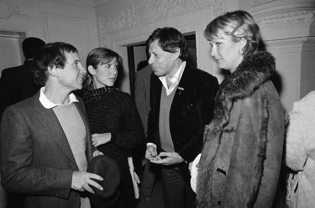 . Entertainer Paul Simon, left, and his date Carrie Fisher chat with her father Eddie Fisher, April 21, 1981 at New York\'s Savoy music hall following a performance by Count Basie. Woman at right is Lindsay Davis. (AP Photo/David Handschuh)