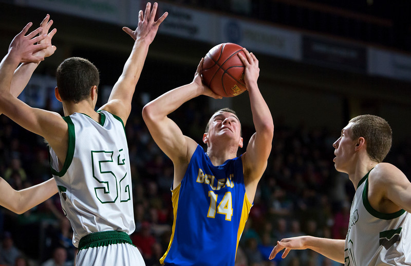 BANGOR, Maine -- 02/17/2017 -- Belfast's Dakota Doolan (center) tries for two past Mount Desert Island's Derek Collins during their Class B boys basketball quarterfinal game at the Cross Insurance Center in Bangor Friday. Ashley L. Conti | BDN