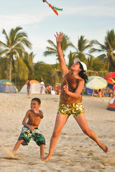 A family plays on the beach.