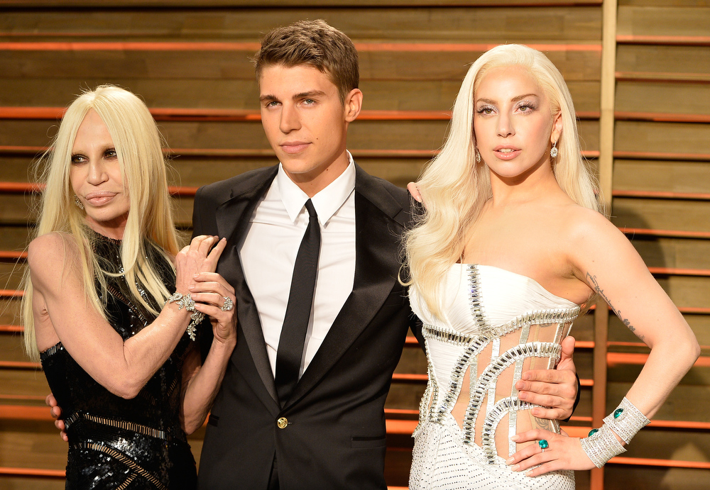 Description of . Designer Donatella Versace, actor Nolan Gerard Funk and Musician Lady Gaga attend the 2014 Vanity Fair Oscar Party hosted by Graydon Carter on March 2, 2014 in West Hollywood, California.  (Photo by Pascal Le Segretain/Getty Images)