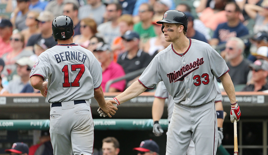 . Minnesota\'s Doug Bernier, left, is congratulated by teammate Justin Morneau after scoring what proved to be the game\'s winning run on a double to right center field from Chris Herrmann during the eight inning against the Tigers.  (Photo by Leon Halip/Getty Images)
